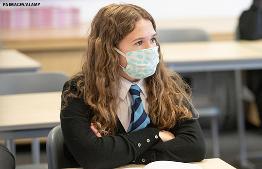 A student wearing a mask in the classroom